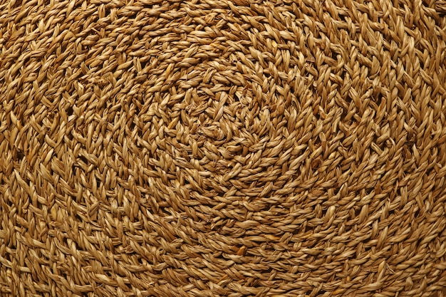 Artistic pattern of golden brown woven sedge place mat surface