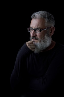 Artistic portrait of a brutal gray haired man with a beard and glasses on a black background, selective focus