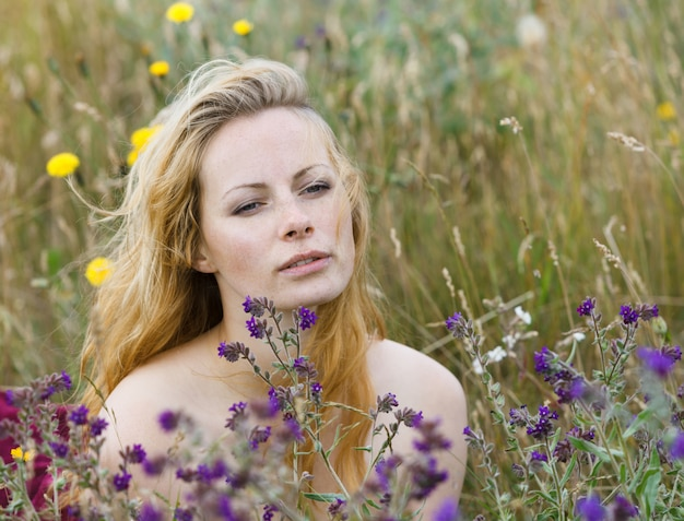Artistic portrait of freckled woman on natural field. young woman enjoying nature among the flowers and grass. close up summer portrait