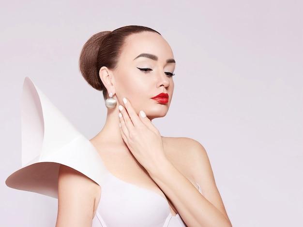 白いドレスを着た美しくエレガントな女性の芸術的な肖像画。エレガントなスタイル。ゴールドジュエリーのファッショナブルなモデル。