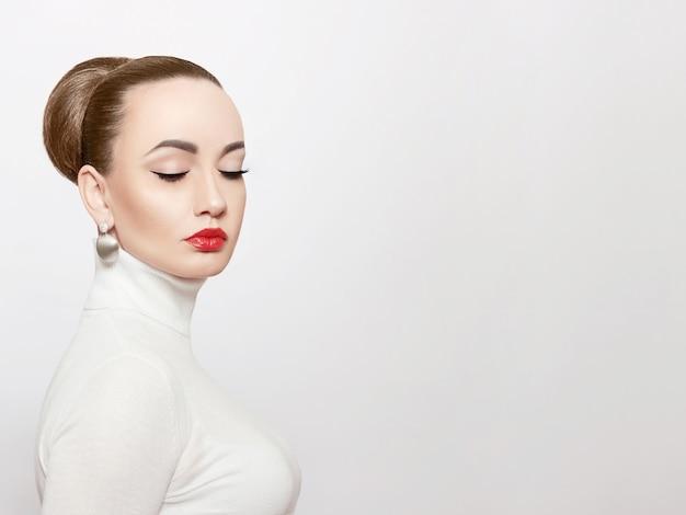 白いタートルネックの美しくエレガントな女性の芸術的な肖像画。エレガントなスタイル。ゴールドジュエリーのファッショナブルなモデル。