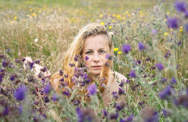 자연 분야에 주근깨가 여자의 예술적 초상화. 꽃과 잔디 사이에서 자연을 즐기는 젊은 여자. 여름 초상화를 닫습니다