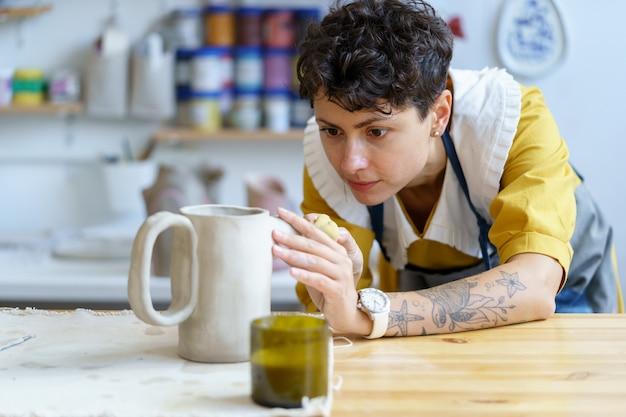 예술적 도예가 여성은 예술 스튜디오나 작업장에서 도자기 도구를 사용하여 주전자 조각 그릇에서 일합니다.