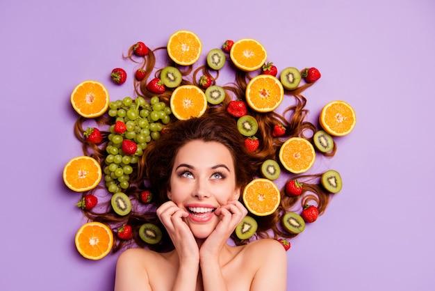 Художественная рыжая женщина позирует с фруктами в волосах