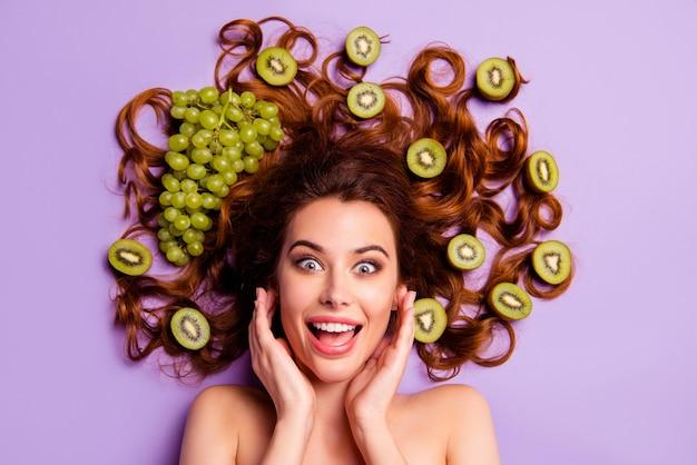 Художественная рыжая женщина позирует с киви и виноградом в волосах