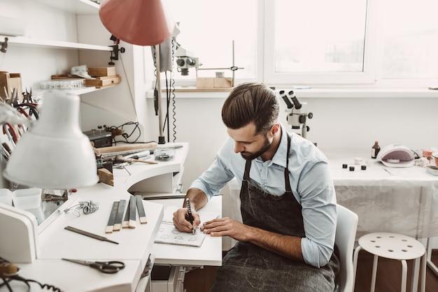 예술적 능력. 수염을 기른 젊은 보석상이 작업실에서 스케치를 그리고 있다