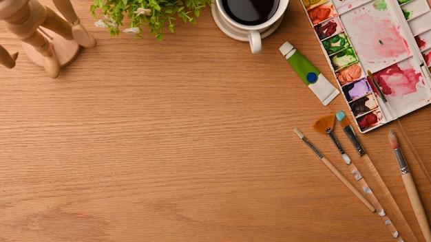 Художественная концепция рабочего места студента с инструментами для рисования и копией пространства на деревянном фоне