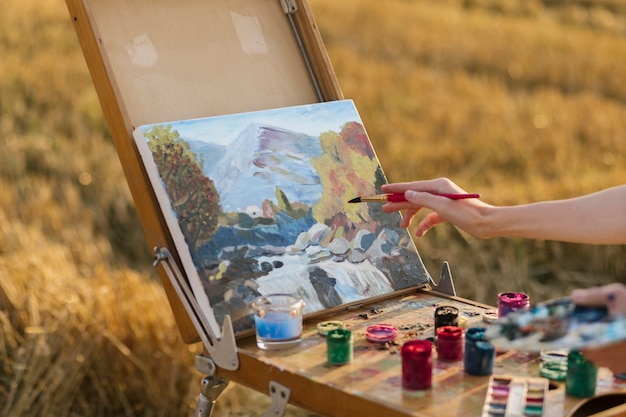 Artistic woman painting in the nature