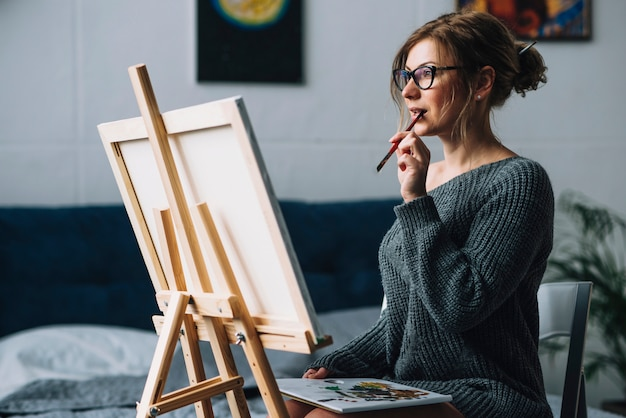 Artistic woman staring at canvas