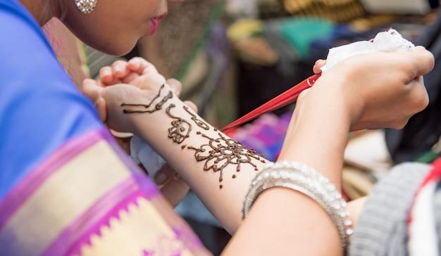 女性の手にヘナタトゥーを適用するアーティスト。一時的な刺青は伝統的なインドの装飾芸術です。