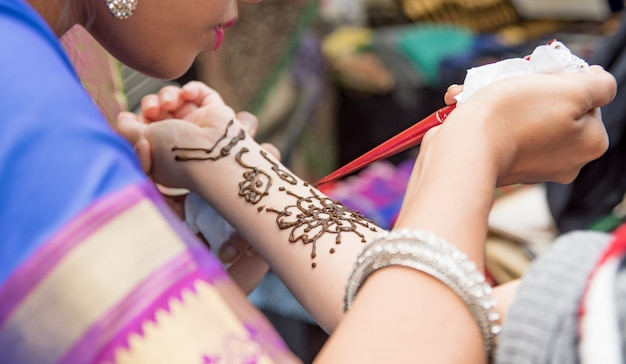 Artists applying henna tattoo on women's hands. mehndi is traditional indian decorative art.