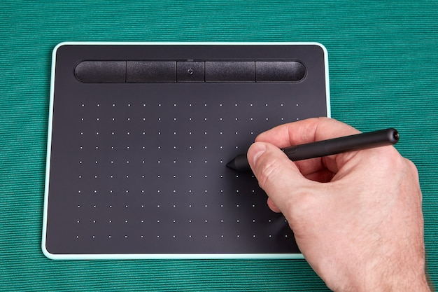 Artists holds  stylus, or pen over screen of graphic tablet, this is an input device when using image processing programs.