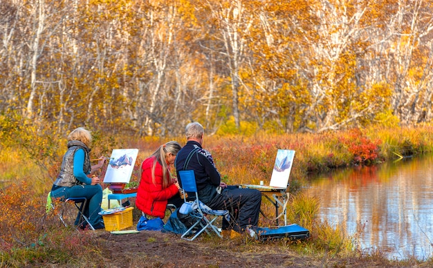 Artists painting landscape in the open air on the lake.