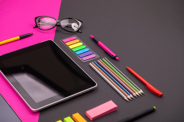 Изображение современного artspace с планшета, очки, канцтовары и смартфон на розовый и черный.