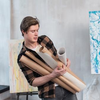 Artsy uomo che tiene i suoi dipinti