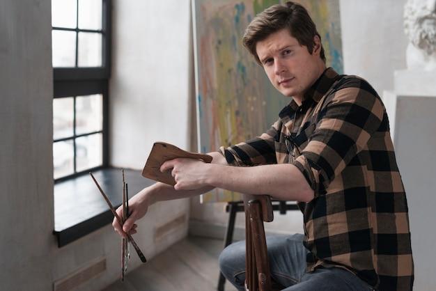 Вычурный мужчина позирует с инструментами рисования