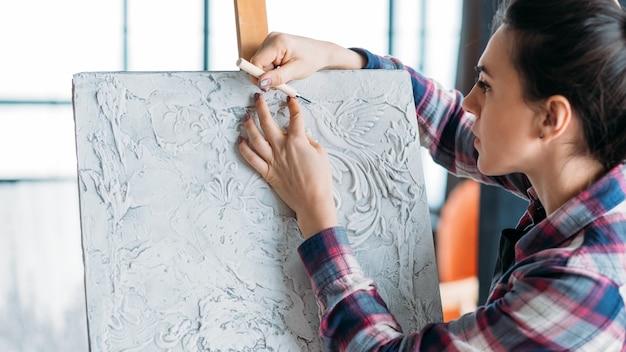 進行中のアートワーク。集中力とインスピレーション。ツール彫刻の女性アーティスト。イーゼルの帆布