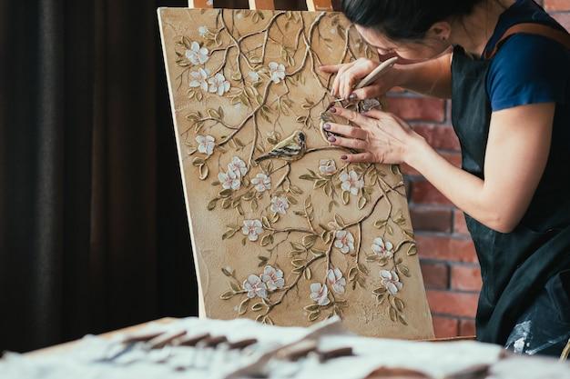 進行中のアートワーク。インスピレーション。ツール作成の女性アーティスト。イーゼルのキャンバス。花や鳥のパターンのテクスチャ。