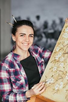 進行中のアートワーク。スタジオのインスピレーション。ツールで笑顔の女性アーティスト。イーゼルのキャンバス。花や鳥のパターンのテクスチャ。