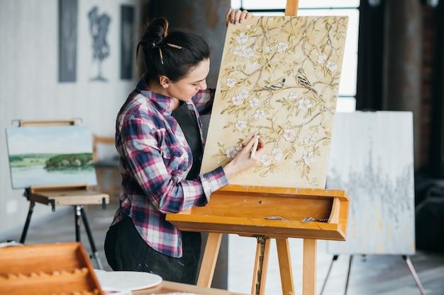 進行中のアートワーク。スタジオのインスピレーション。ツール作成の女性アーティスト。イーゼルのキャンバス。花や鳥のパターンのテクスチャ。