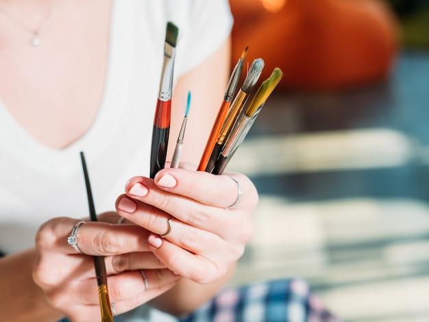 Инструменты для художественных работ. рабочее место студии. ассортимент кистей в крупном плане рук художника.