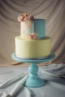 アートワーク。ピンクの花でパステルスタイルで飾られたウェディングケーキ