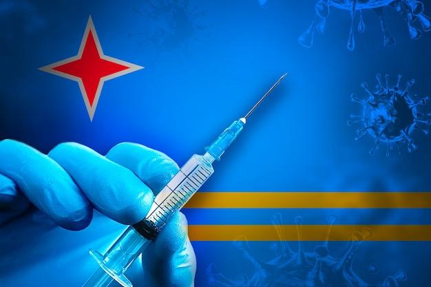 Aruba covid19 예방 접종 캠페인 파란색 고무 장갑을 끼고 깃발 앞에 주사기를 들고 있습니다.