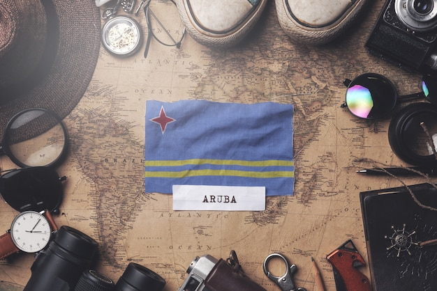 Флаг арубы между аксессуарами путешественника на старой винтажной карте. верхний выстрел
