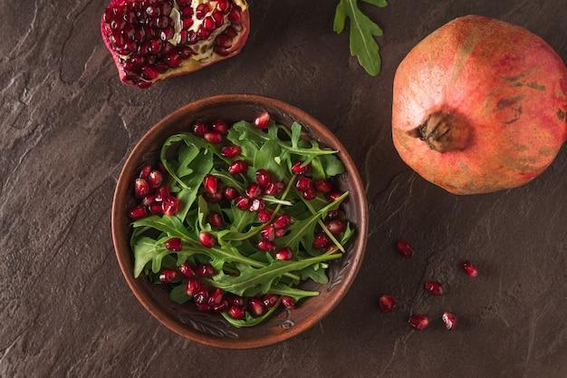 ルッコラとザクロの葉は、石のテーブルの上の粘土のボウルに入れます。ダイエットベジタリアンサラダ。フラットレイ。