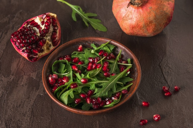 Arugula와 석류는 돌 테이블에 점토 그릇에 나뭇잎. 다이어트 채식 샐러드.