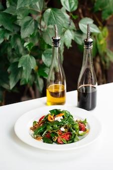 흰색 테이블에 소스와 함께 arugula와 새우 샐러드