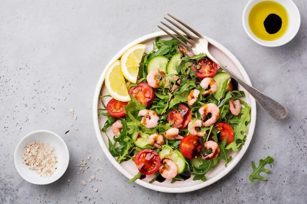 Arugula, 오이, 토마토 및 새우 샐러드와 세라믹 접시에 간장