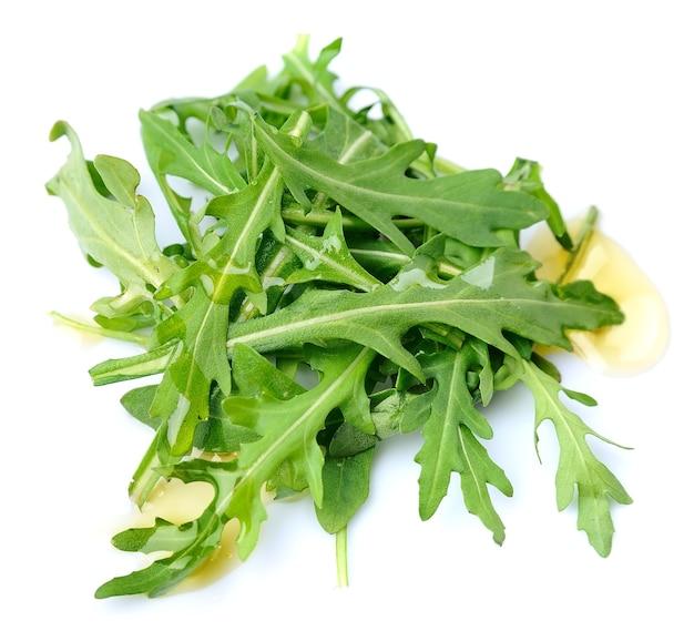ルッコラは白で分離された油でサラダを残します