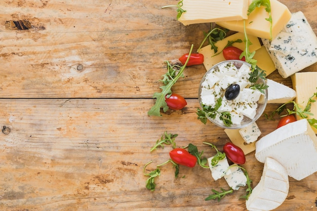 Arugula leaves with tomatoes; cheese blocks on wooden textured backdrop