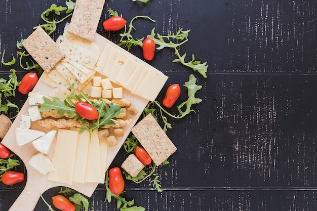 Arugula leaves with tomatoes, cheese, breadsticks and crisp bread on black textured backdrop