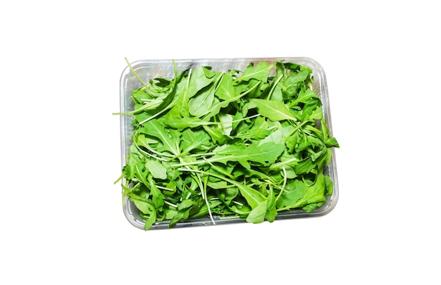 白い背景で隔離のプラスチックの箱のルッコラサラダ。ルッコラレタスの健康食品。ベジタリアンライフスタイルのコンセプト。緑の新鮮なビタミン。