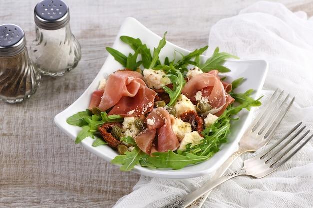 Салат из рукколы, прошутто с вялеными помидорами, ломтики моцареллы, каперсы, заправленные оливковым маслом и пармезаном. блюдо для тех, кто следит за своим здоровьем