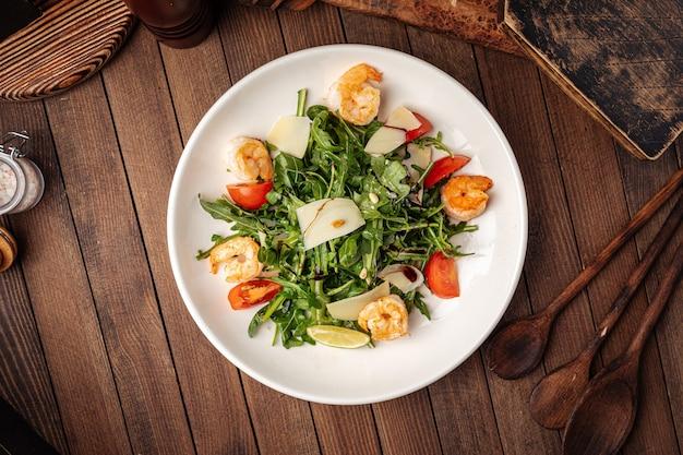 Салат из рукколы с креветками на деревянных фоне