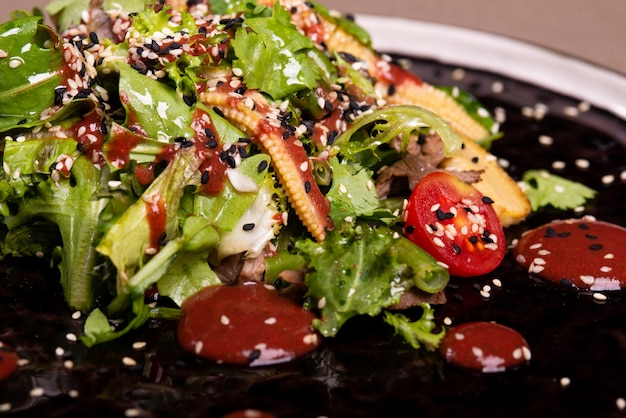 Arugula, tomato and meat salad on a black plate with restaurant serving