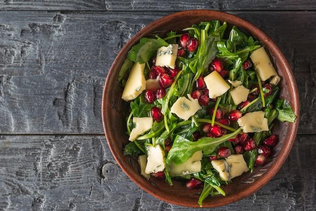 석류와 나무 테이블에 접시에 파란색 곰팡이와 치즈 arugula. 다이어트 채식 샐러드. 평평하다.