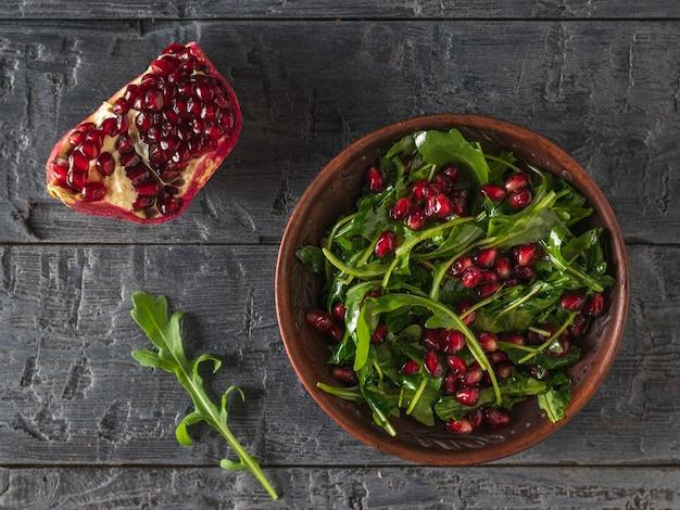 석류 씨와 나무 테이블에 점토 그릇에 올리브 오일 arugula. 평평하다. 다이어트 채식 샐러드.