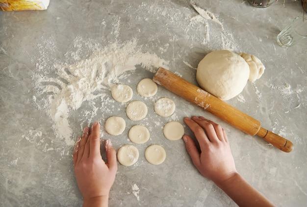 Вырезанные круглые формы, тесто и скалка на присыпанном мукой столе на кухне.