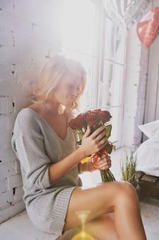 花のように美しい。花束を持って寝室の床に座って笑っている魅力的な若い女性