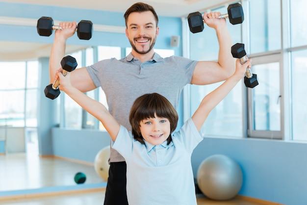 私の父と同じくらい強い。健康クラブに立っている間、ダンベルで運動し、カメラを見ている幸せな父と息子