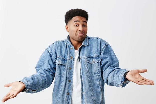 As you say, bro. no problem. isolated on white portrait of funny dark-skinned man in white t-shirt and denim jacket spreading hands with unsure face expression.