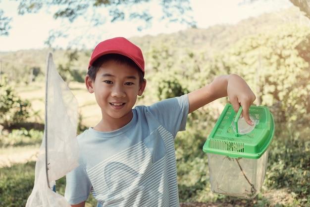 ネットでバタフライを捕まえ、昆虫の箱を保持するasainの少年