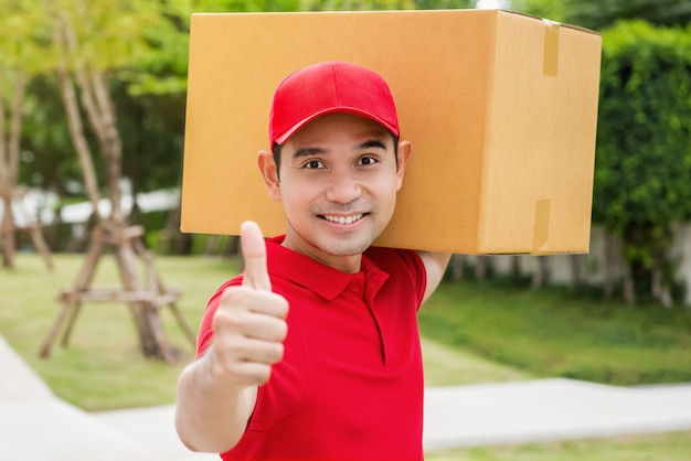 Asain delivery man holds a box with thumbs up.