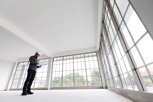 Инженер asain в белом шлеме с синим принтом проверяет строительную комнату