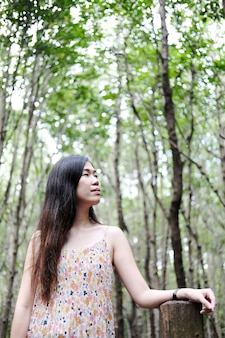 Asain girl is smiling and sitting on wooden bridge in the tropical mangrove forest