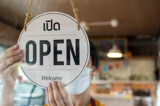보호용 얼굴 마스크를 쓴 아사인 직원 여성은 카페 커피숍, 호텔 서비스, 카페 레스토랑, 소매점, 소규모 비즈니스 소유자 개념의 유리문에 태국어로 된 열린 간판을 돌리고 있습니다.